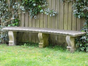 A curved natural limestone garden bench