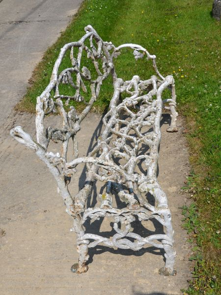 A 19th century cast iron garden seat of twig and foliage design