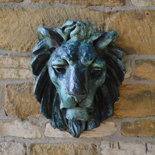 A modern bronze lion mask wall spout