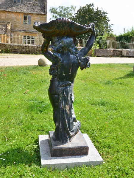 A large cast iron figure holding aloft a conch shell by the Durenne Foundry