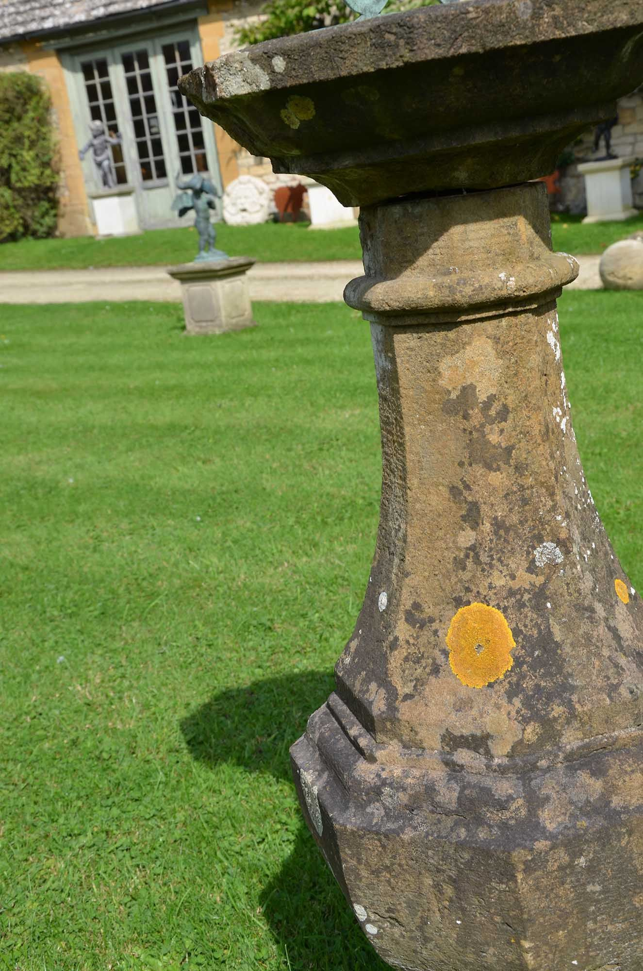 An early 20th century carved natural Horton stone sundial of octagonal form with bronze sundial plate