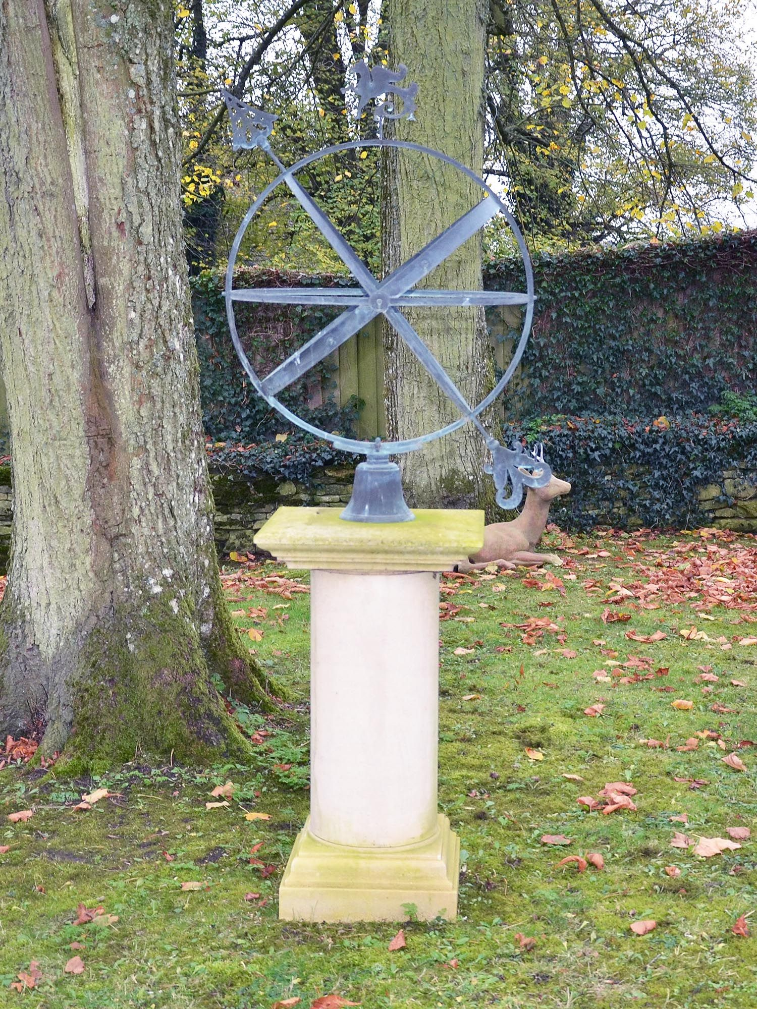 A carved Bath stone pedestal base supporting a Greenwich armillary sphere with griffin