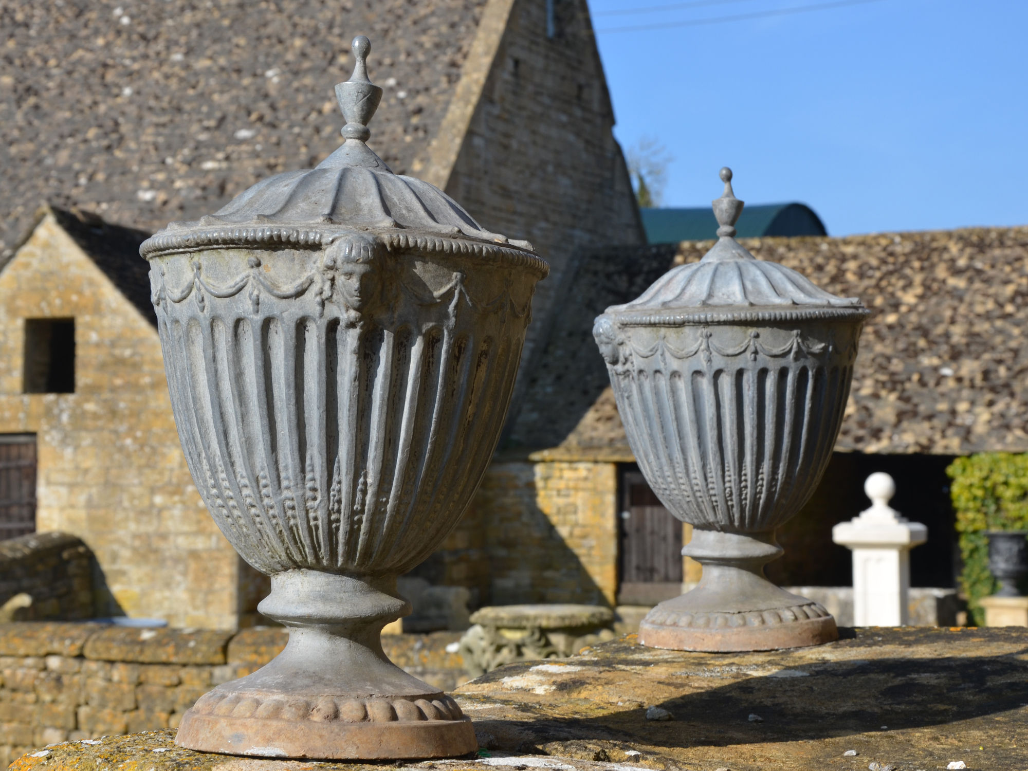 A pair of lead finial urns in the Adams style
