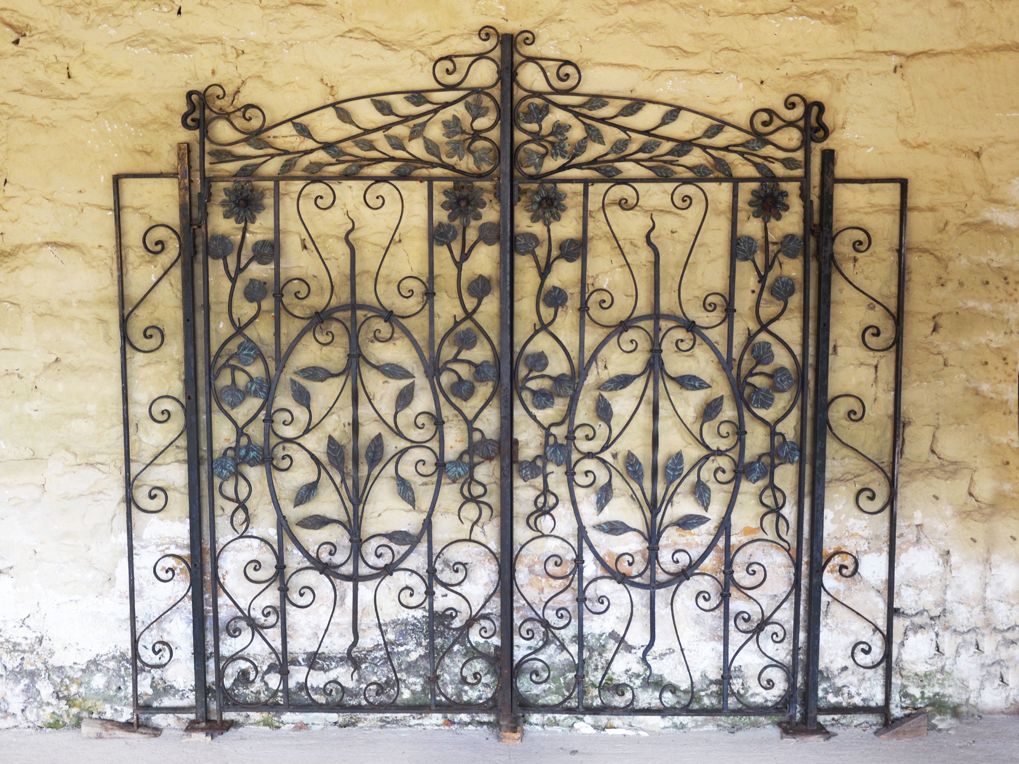 A pair of decorative wrought iron gates having leaf and flower motif throughout