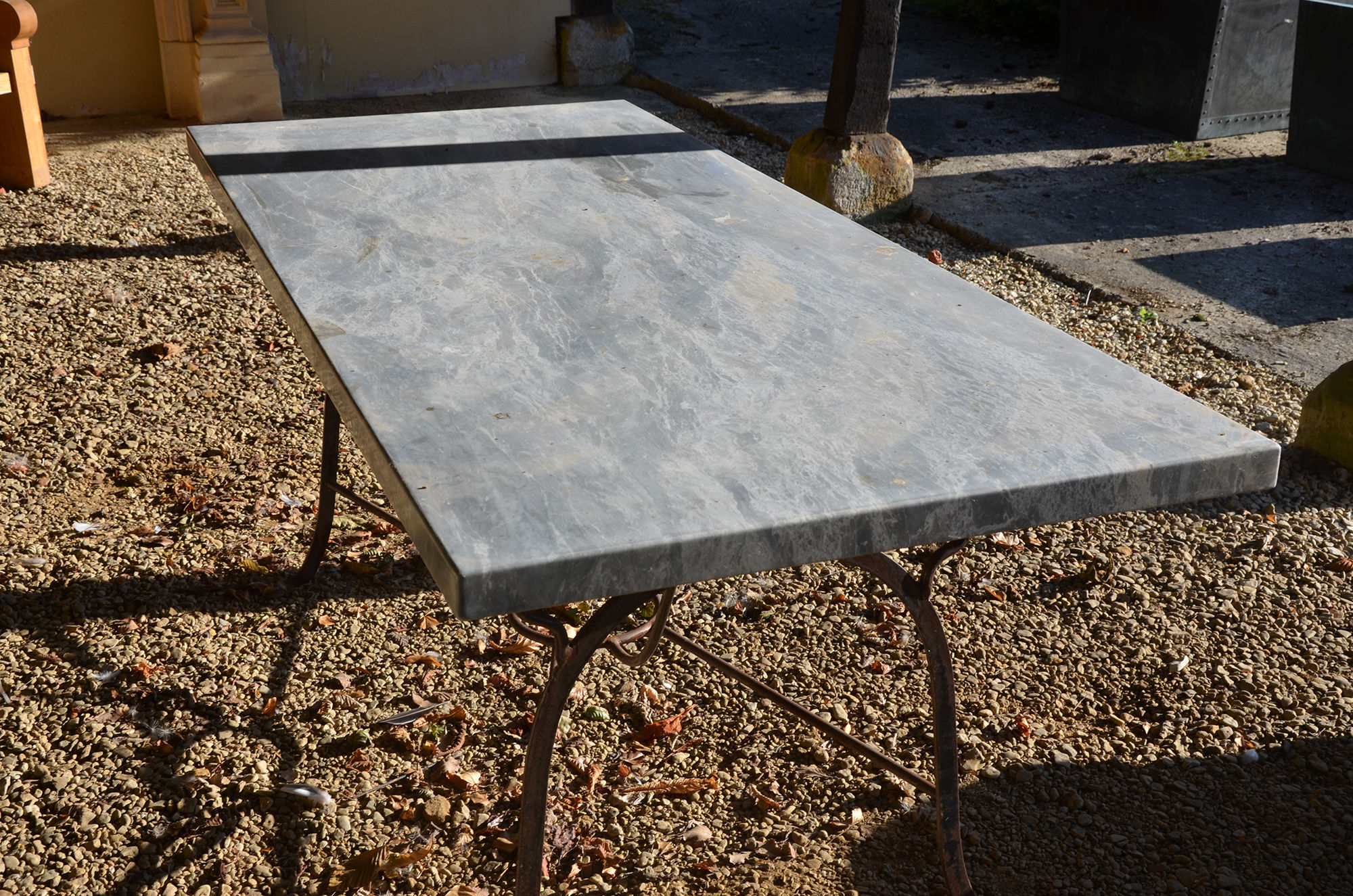 A wrought iron table base with solid Italian Arabesque marble top
