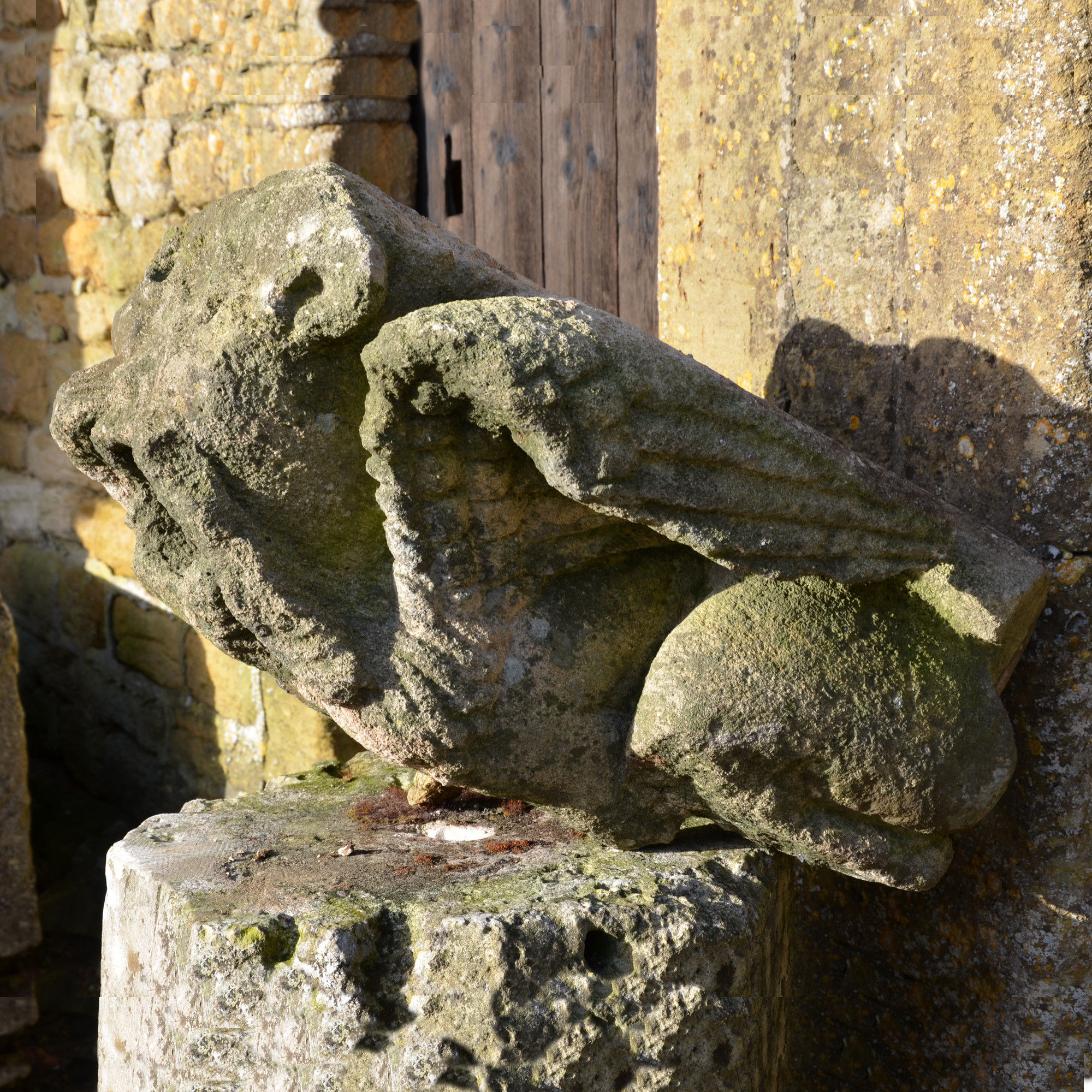 A large medieval carved limestone long fingered mouth puller gargoyle